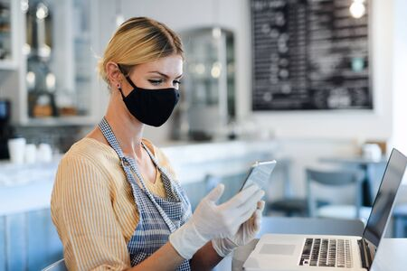 Coffee shop woman owner working with face mask, open after lockdown quarantine. Foto de archivo - 146660565