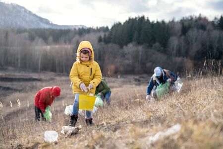 Group of activists picking up litter in nature, environmental pollution and plogging concept.