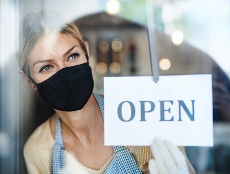 Coffee shop woman owner with face mask, open after lockdown quarantine.