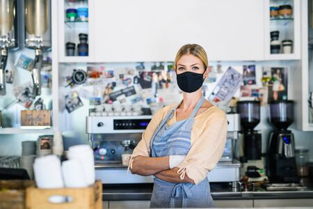 Woman owner with face mask in coffee shop, lockdown and back to normal concept. Фото со стока