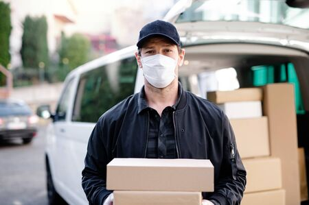 Delivery man courier with face mask delivering parcel boxes in town. Stock Photo