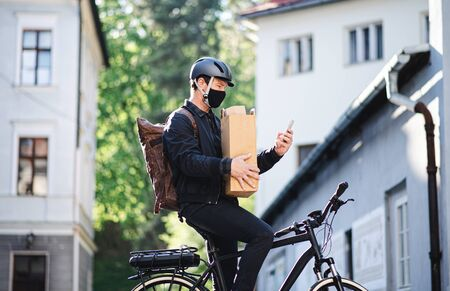 Delivery man courier with face mask and bicycle using smartphone in town. Stock Photo