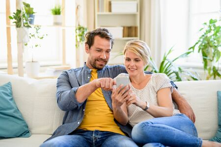 Happy couple in love sitting indoors at home, using smartphone.