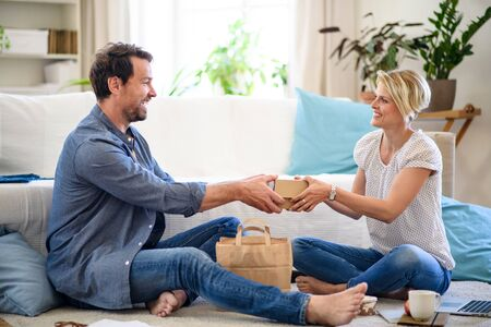 Couple sitting on floor indoors at home, food delivery service concept.