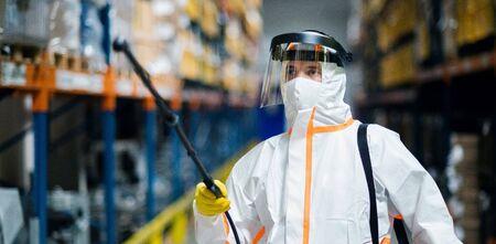 Uomo lavoratore con maschera protettiva e tuta disinfettante fabbrica industriale con pistola a spruzzo.