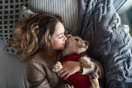 Top view of young woman relaxing indoors on sofa at home with pet dog.