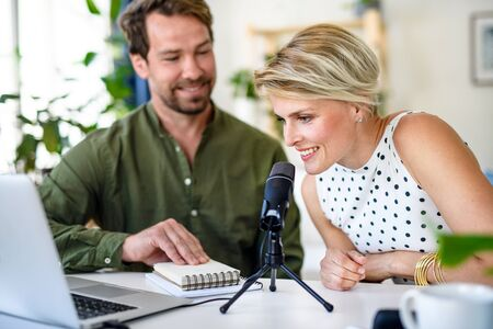 Happy couple with microphone having video call on laptop indoors at home. Фото со стока
