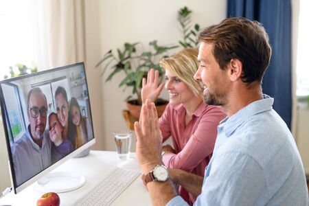 Happy couple having video call with friends on computer indoors at home, waving.