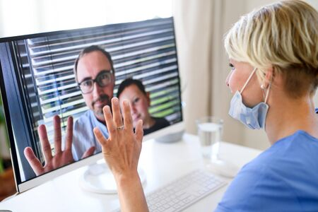 Woman doctor having video call with husband and son on laptop. Фото со стока