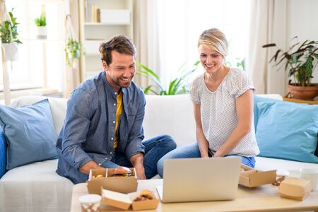 Happy couple with hamburgers sitting on sofa indoors at home, using laptop.