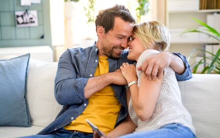 Happy couple in love sitting indoors at home, hugging.