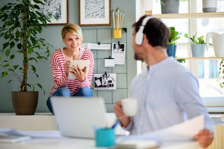 Mature businessman working and talking to colleague indoors in office.
