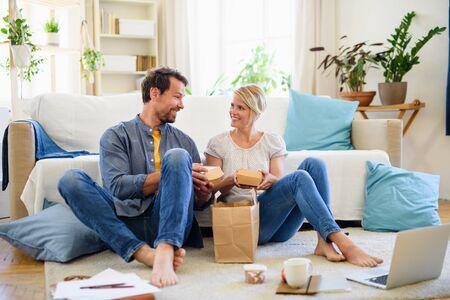 Happy couple sitting on floor indoors at home, eating hamburgers. Фото со стока