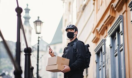 Delivery man courier with face mask and smartphone delivering in town. Stock fotó