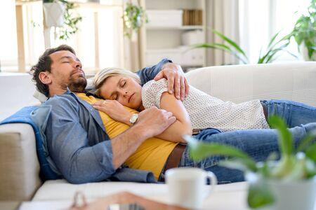 Happy couple in love on sofa indoors at home, sleeping. Фото со стока