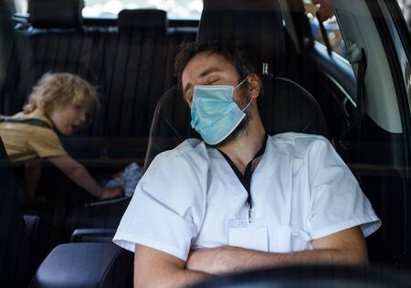 Tired and exhausted doctor sitting in car after long and difficult shift, sleeping.