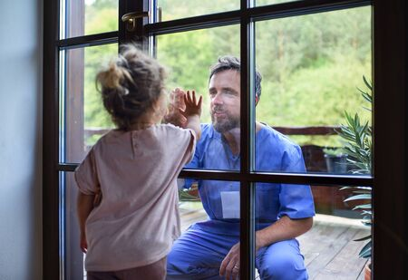 Doctor coming to see family in isolation, window glass separating them.
