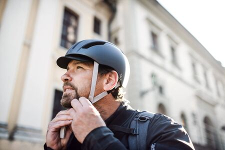 Delivery man courier fastening bicycle helmet in town. Stock Photo