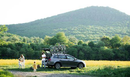 Famille avec deux petits enfants et des masques faciaux partant en voyage à vélo à la campagne. Banque d'images