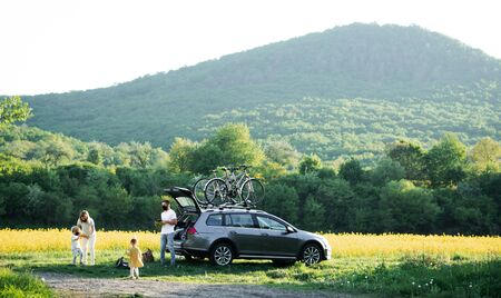 Family with two small children and face masks going on cycling trip in countryside.