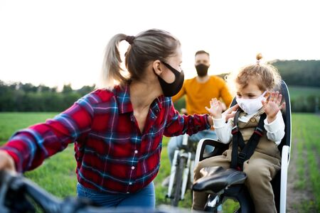 Family with two small children on cycling trip, wearing face masks.
