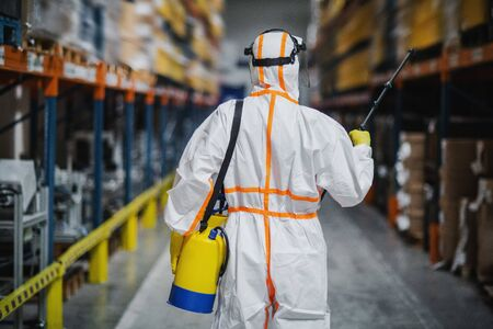 Rear view of man worker with protective suit disinfecting industrial factory with spray gun.