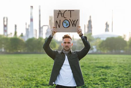 Young activist with placard standing outdoors by oil refinery, protesting.