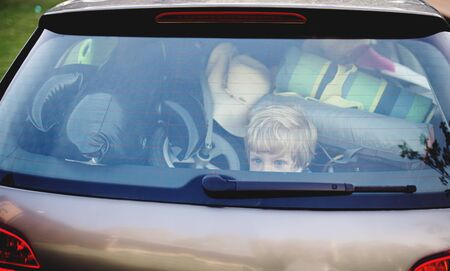 Small boy sitting in loaded car boot with closed door, local trip concept.