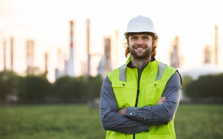 Young engineer standing outdoors by oil refinery, looking at camera.