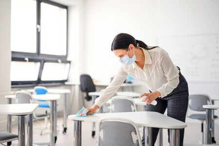 Teacher back at school after covid-19 quarantine and lockdown, disinfecting desks. Stock fotó - 148997758