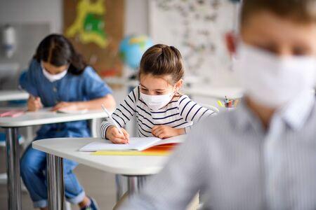 Bambini con maschera facciale tornano a scuola dopo la quarantena e il blocco del covid-19.