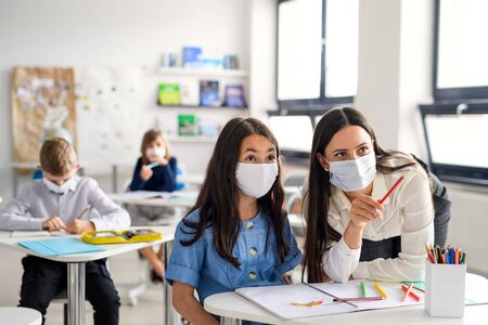 Teacher and children with face mask back at school after covid-19 quarantine and lockdown. Фото со стока - 148997682