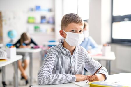 Boy with face mask back at school after covid-19 quarantine and lockdown. Stock Photo - 149357860