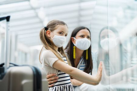 Mutter mit Tochter, die in den Urlaub fährt und am Flughafen Gesichtsmasken trägt.