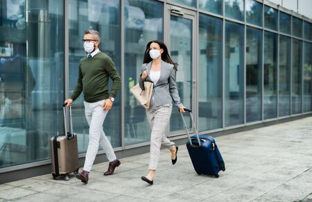 Businesspeople with luggage going on business trip, wearing face masks at the airport.