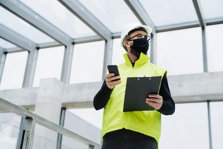Portrait of worker with face mask at the airport, holding smartphone.