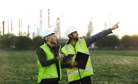Two young engineers with tablet standing outdoors by oil refinery, discussing issues. Stok Fotoğraf