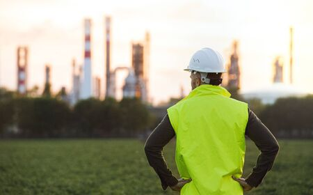 Rear view of young engineer standing outdoors by oil refinery, arms on hips.