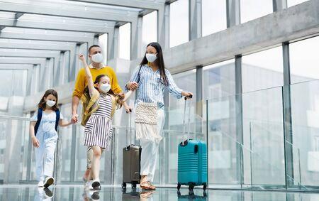 Familie mit zwei Kindern, die am Flughafen in den Urlaub fahren und Gesichtsmasken tragen. Standard-Bild