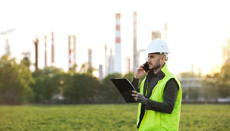 Young engineer with smartphone standing outdoors by oil refinery. Copy space. Stok Fotoğraf