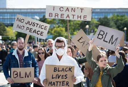 Black lives matters protesters holding signs and marching outdoors in streets.