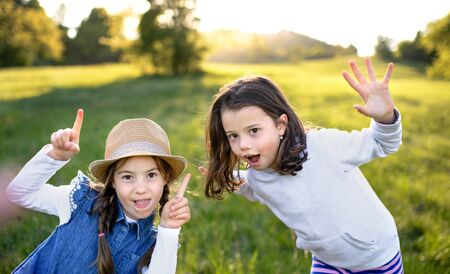 Portrait of two small girls standing outdoors in spring nature, having fun.