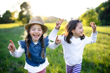 Portrait de deux petites filles debout à l'extérieur dans la nature printanière, en riant. Banque d'images