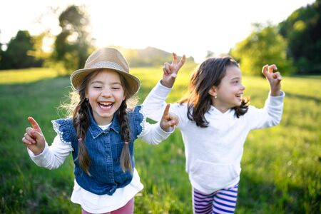 Portrait of two small girls standing outdoors in spring nature, laughing.