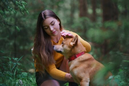 Young woman with a dog on a walk outdoors in summer nature.