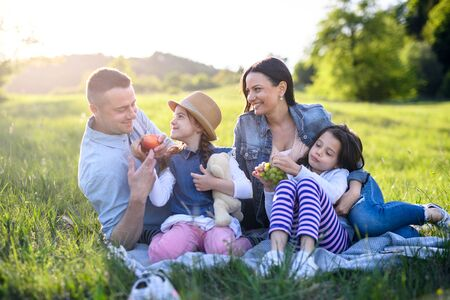 Happy family with two small daughters sitting outdoors in spring nature, having picnic. 스톡 콘텐츠