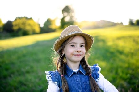 Portrait of small girl standing outdoors in spring nature, looking at camera.