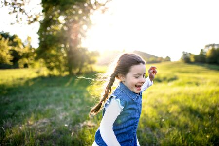 Portrait of small girl running outdoors in spring nature, laughing.