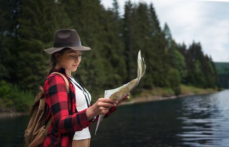 Side view of young woman standing by lake outdoors in summer nature, using map.