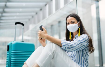 Young woman with smartphone going on holiday, wearing face masks at the airport. Standard-Bild - 149899424